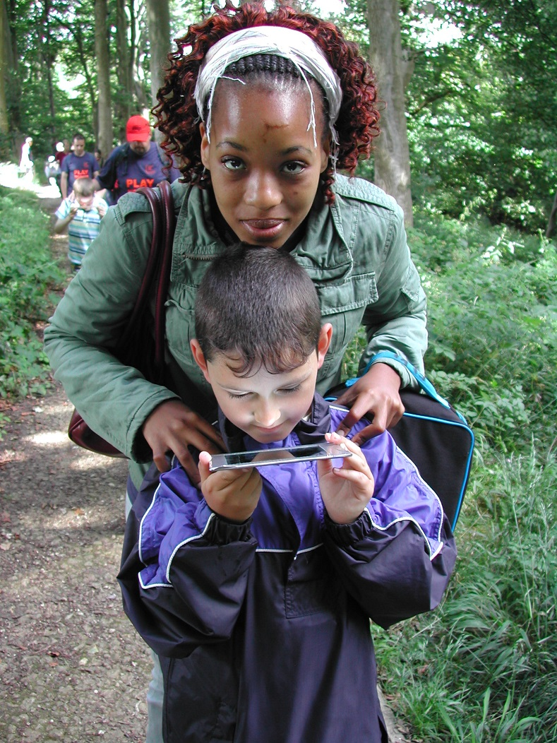 Sensory trail - children from a youth group use a mirror to view the tree tops above them