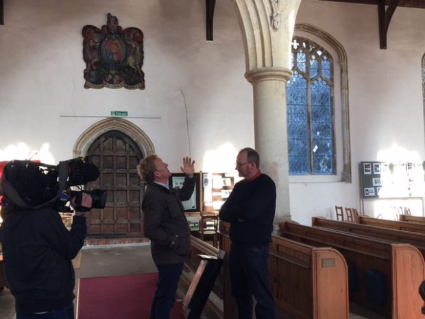 A BBC camera films a presenter looking up into a church for bats with a Natural England expert