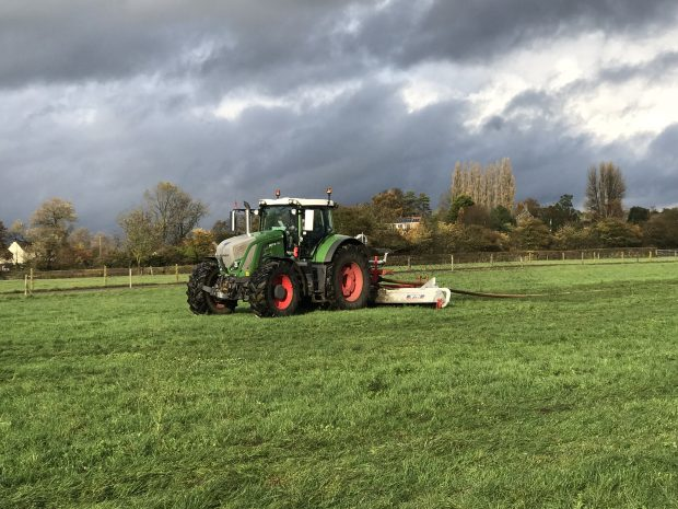 A tractor ploughing a green field