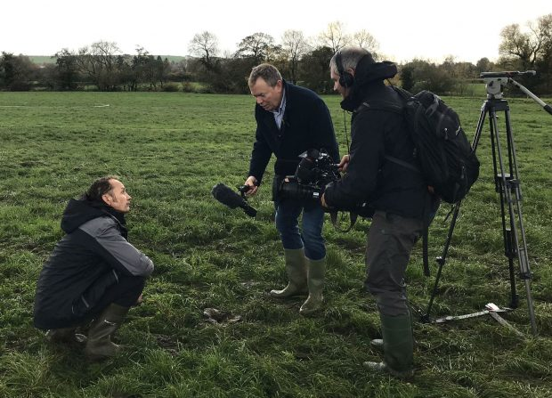 A farmer kneeling in a field while being interviewed by a TV crew