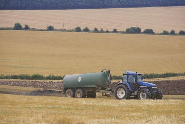 A tractor in a field dragging a trailer