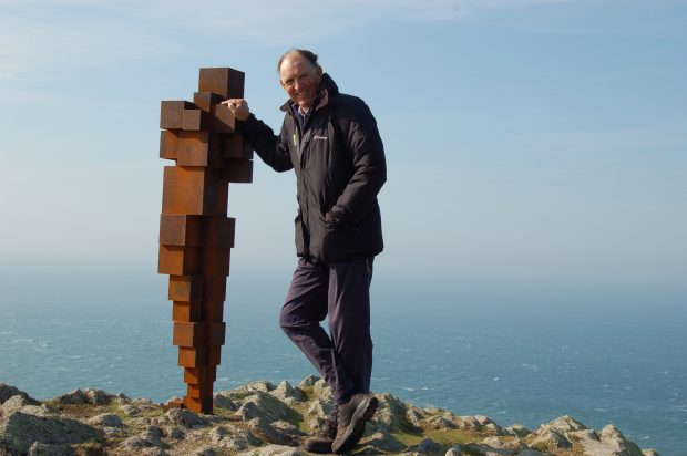 Andrew Sells with Antony Gormley statue on Lundy with the sea in the background