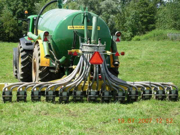 a tractor dragging a slurry injector in a field