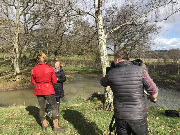 A TV cameraman with his back to the camera in front of an interview with a Natural England by a pond
