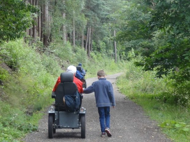 A young children and elderly man in a wheelchair walking down a country lane