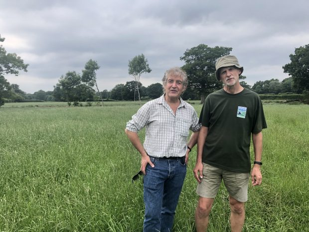 Tony Juniper and Jon Shelton standing in a green field.