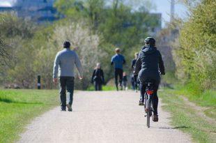 Woman cycling through a park w