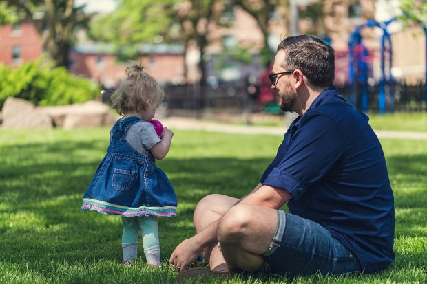 Father and daughter sitting in a park