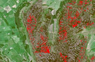 An aerial satellite image of a landscape is seen. Fields are patchworked together and small red sections highlight moorland areas.